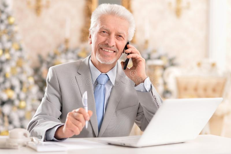 Portrait of happy senior man using laptop at home stock photography