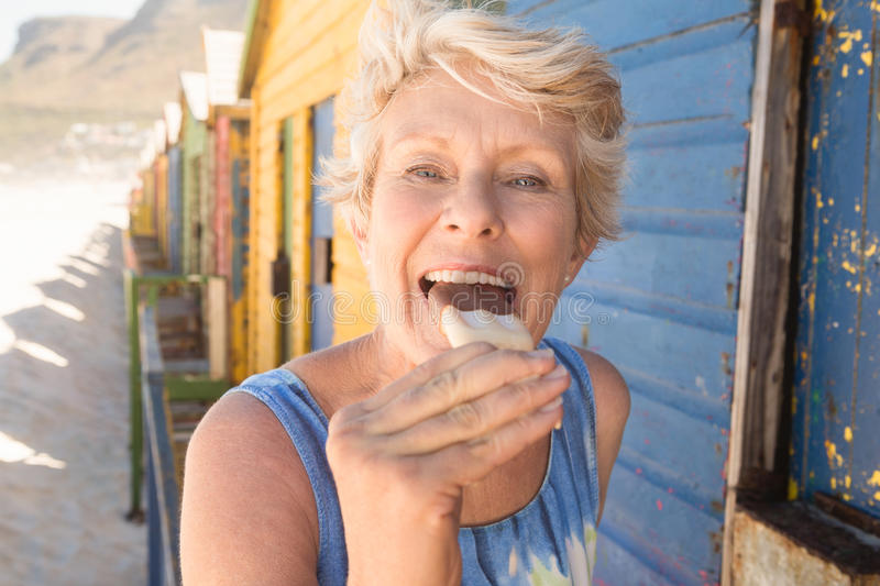 Portrait of happy senior woman eating ice cream while standing by hut royalty free stock photo
