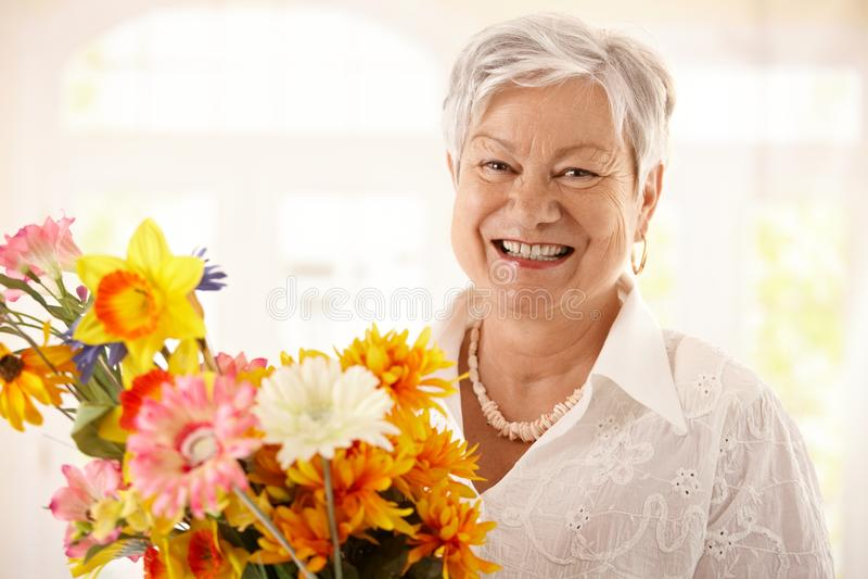 Portrait Of Happy Senior Woman Holding Flowers Stock Photos