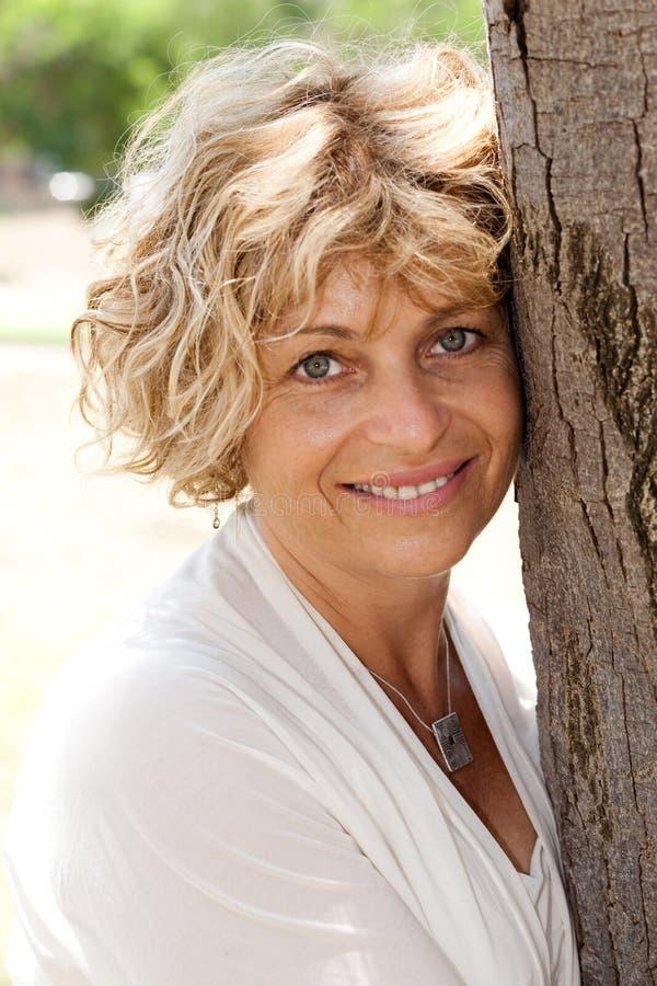 Portrait of a happy senior woman holding tree stock photo
