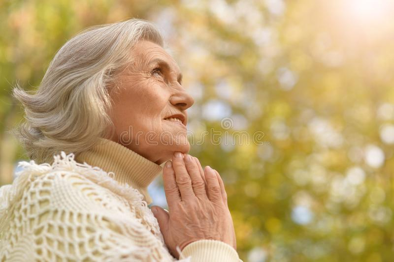 Portrait of a happy senior woman smiling praying royalty free stock images