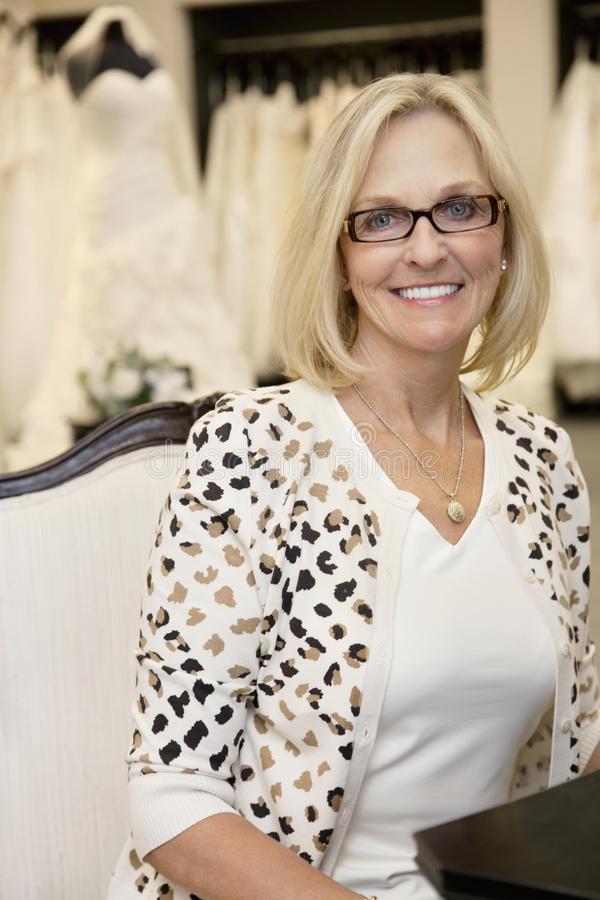 Portrait of a happy senior woman wearing eyeglasses sitting in bridal boutique stock image
