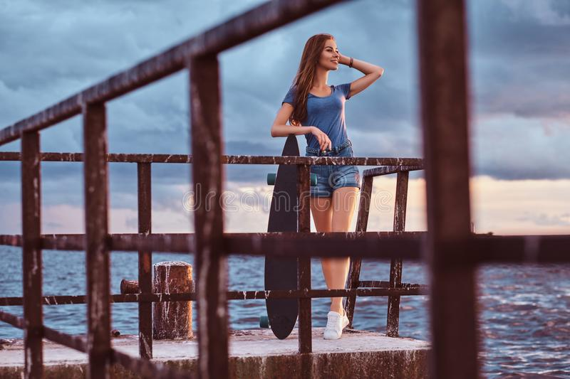 Sensual girl posing with skateboard standing on the old pier is enjoying amazing dark cloudy weather during sunset. royalty free stock photography