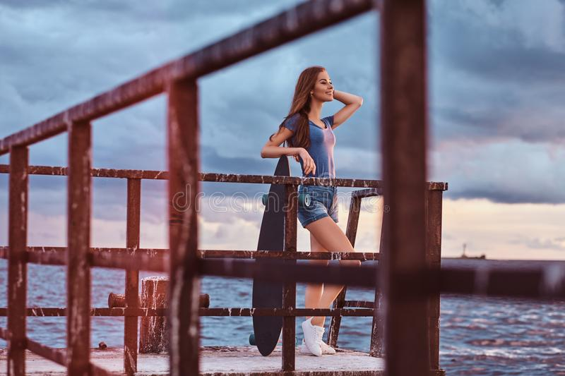 Sensual girl posing with skateboard standing on the old pier is enjoying amazing dark cloudy weather during sunset. royalty free stock photos
