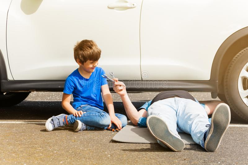 Happy boy helping his father repairing car outside royalty free stock images