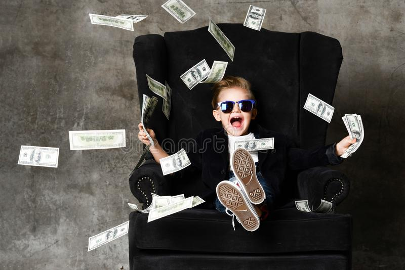 Portrait of happy shouting self-confident rich kid boy millionaire sitting in luxury armchair and throwing money dollars cash stock photos
