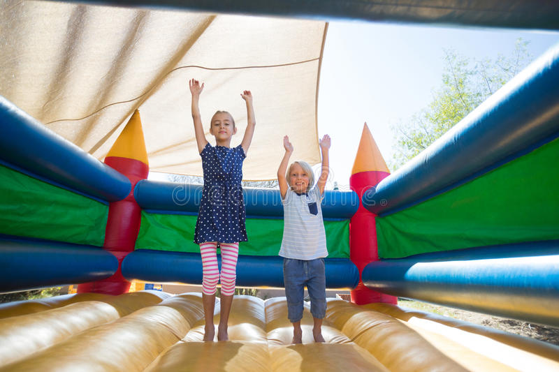 Portrait of happy siblings with arms raised jumping on bouncy castle royalty free stock photo