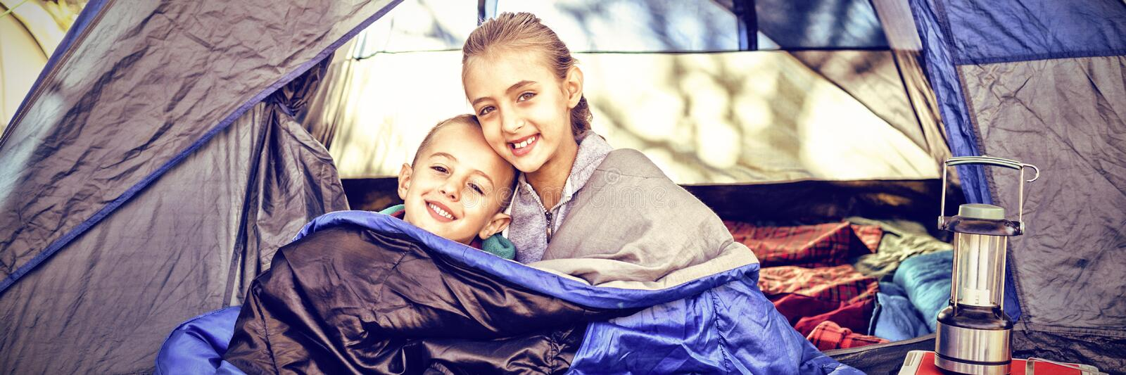 Happy siblings sitting in the tent stock image