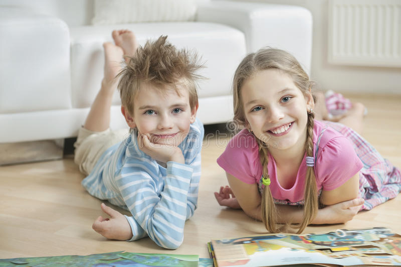 Portrait of happy siblings with story books lying on floor in living room stock photo