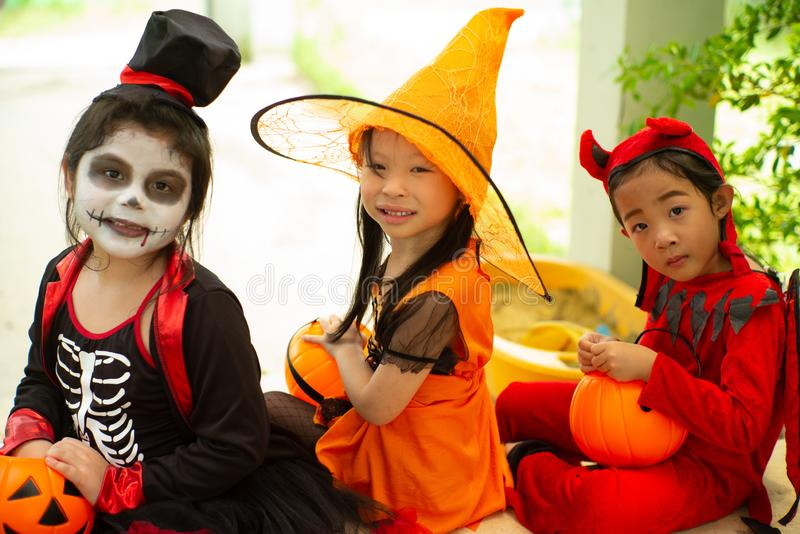 Portrait of happy sisters in Halloween costume sitting in front. Of the door and waiting for playing Trick or treat. Happy Halloween days royalty free stock photo