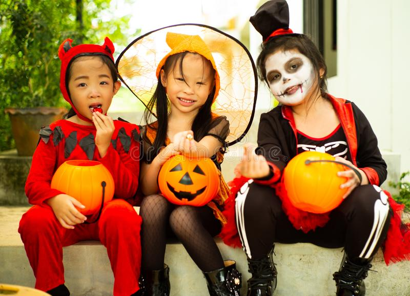 Portrait of happy sisters in Halloween costume sitting in front. Of the door and waiting for playing Trick or treat. Happy Halloween days royalty free stock images