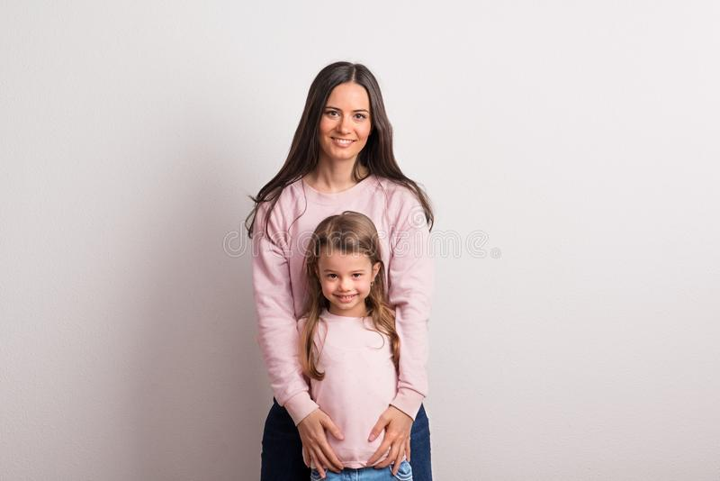 A portrait of a small girl and her mother standing in a studio against white wall. royalty free stock photo
