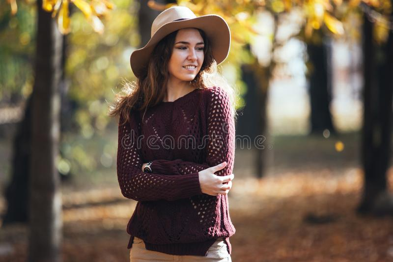 Portrait of happy smile young woman outdoors in autumn park in cozy sweater and hat. Warm sunny weather. Fall concept royalty free stock photos