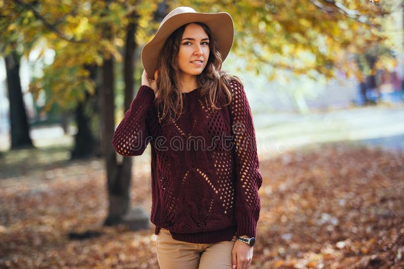 Portrait of happy smile young woman walking outdoors in autumn park in cozy sweater and hat. Warm sunny weather. Fall stock photos