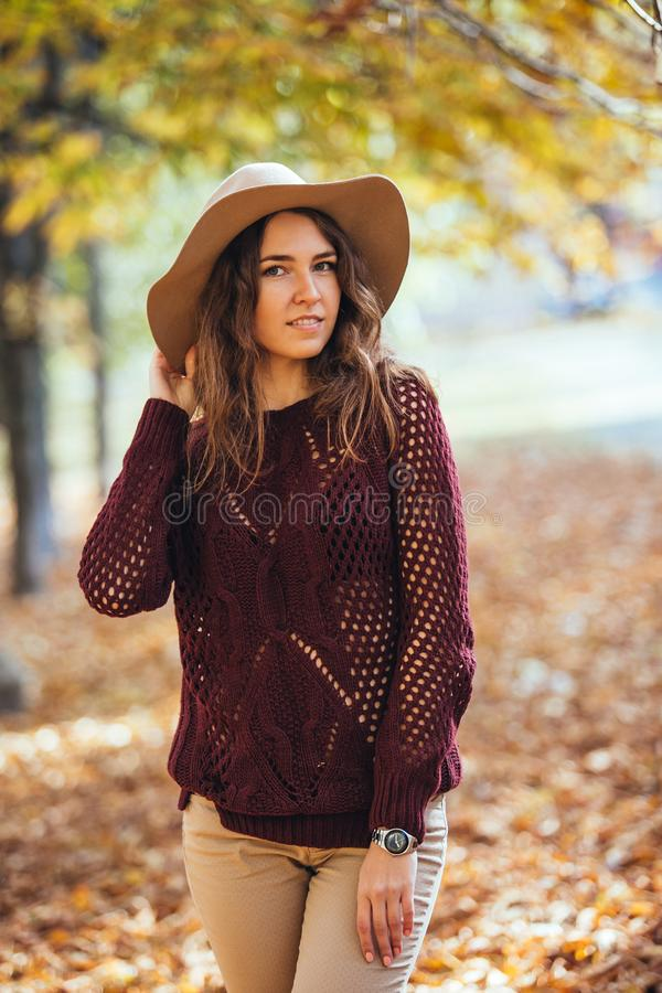 Portrait of happy smile young woman walking outdoors in autumn park in cozy sweater and hat. Warm sunny weather. Fall royalty free stock image