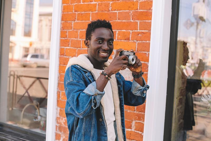 Portrait happy smiling african man with vintage film camera taking picture walking on city street over brick wall. Background stock photography