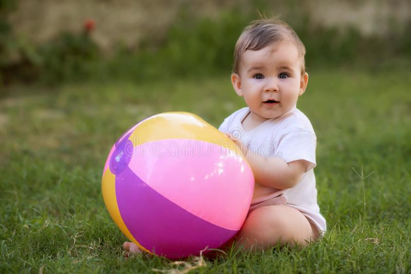 Portrait of Happy Smiling Baby Boy Playing with Toys in Backyard Garden in Summer Season stock image