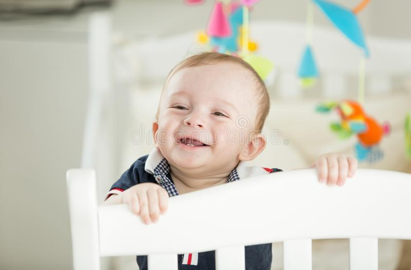 Portrait of happy smiling baby boy with 2 teeth standing in crib royalty free stock images