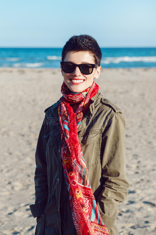 Portrait of happy smiling beautiful Caucasian white brunette woman with short hair in green jacket, red scarf and sunglasses royalty free stock photography
