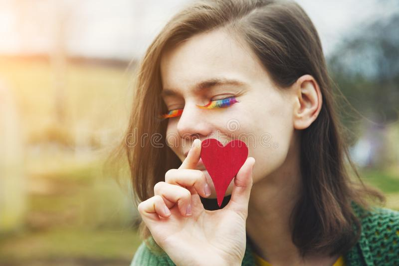 Portrait of happy smiling beautiful young woman with rainbow lgbtq eyelashes holding red wooden heart next to her face royalty free stock images