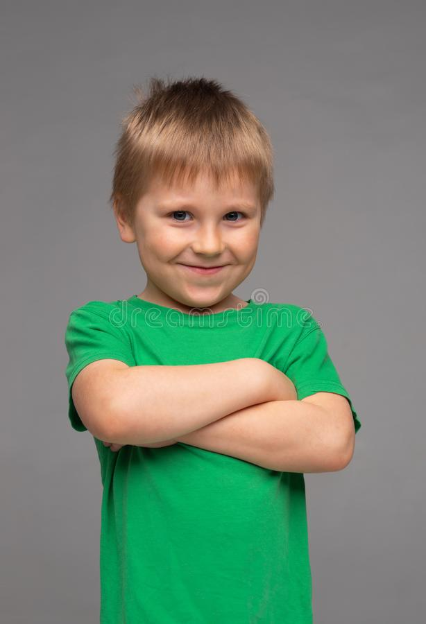 Portrait of happy smiling boy in green t-shirt. Attractive kid in studio. Childhood concept. stock photography