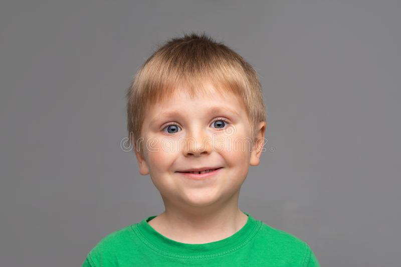 Portrait of happy smiling boy in green t-shirt. Attractive kid in studio. Childhood concept. royalty free stock image
