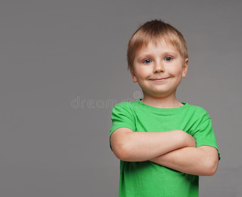 Portrait of happy smiling boy in green t-shirt. Attractive kid in studio. Childhood concept. stock images