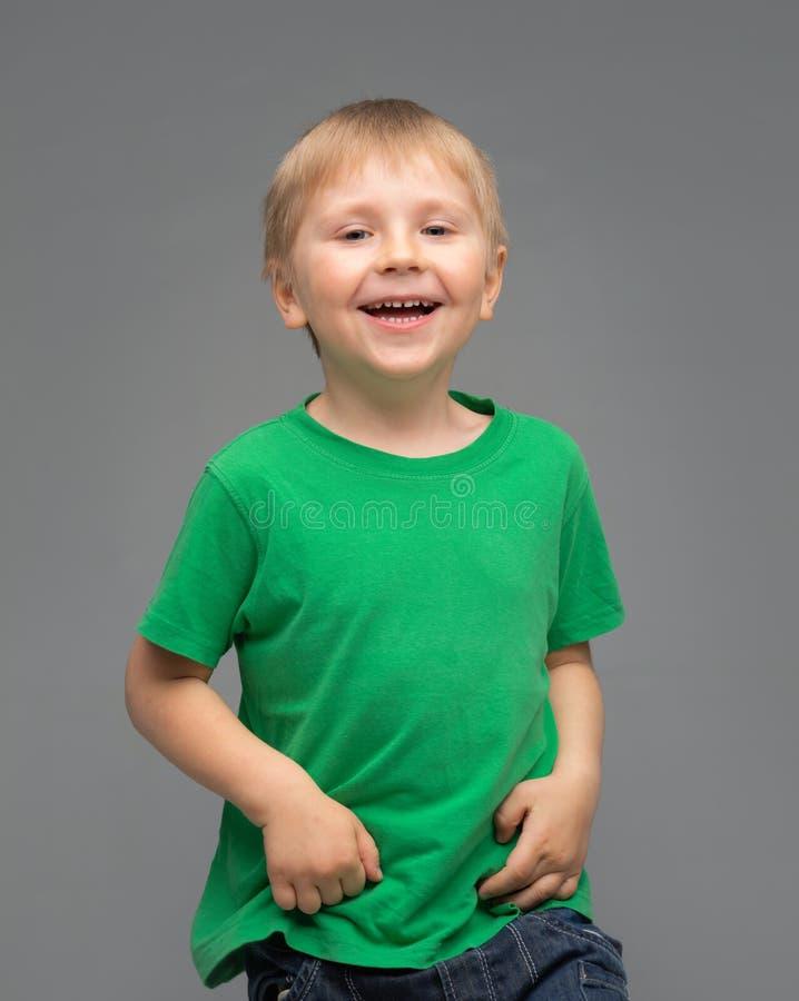 Portrait of happy smiling boy in green t-shirt. Attractive kid in studio. Childhood concept. stock photos