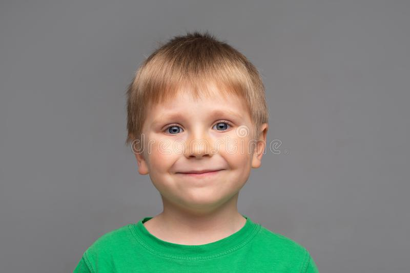 Portrait of happy smiling boy in green t-shirt. Attractive kid in studio. Childhood concept. royalty free stock photos