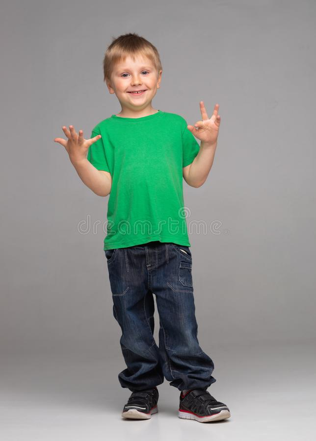Portrait of happy smiling boy in green t-shirt and jeans. Attractive kid in studio. stock photos