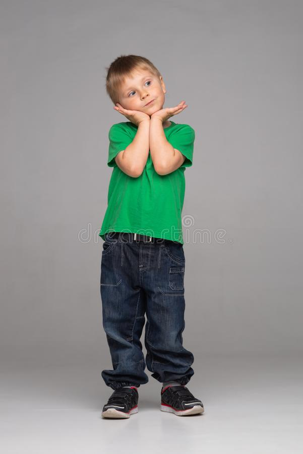 Portrait of happy smiling boy in green t-shirt and jeans. Attractive kid in studio. stock images