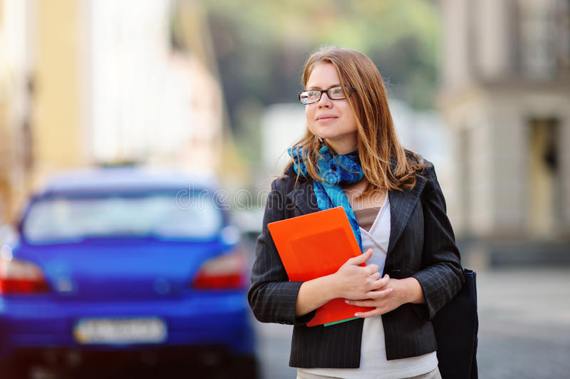 Portrait of happy smiling business woman with red folder in city royalty free stock images