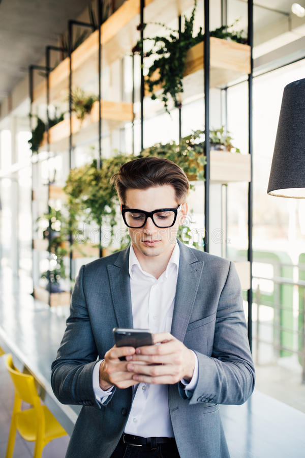 Portrait of a happy smiling businessman in eyeglasses using smartphone while sitting at the office stock image