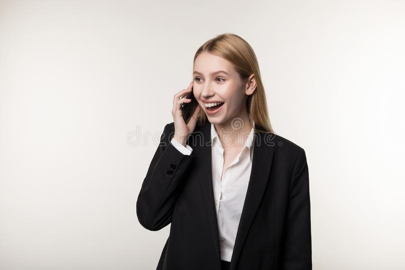 Portrait of happy smiling businesswoman dressed in black suit use phone royalty free stock photo