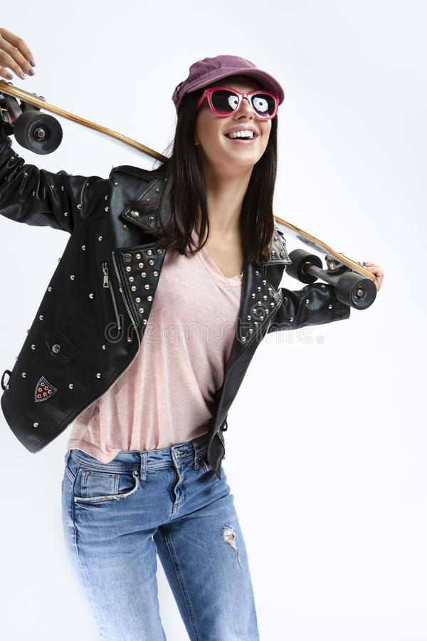 Portrait of Happy Smiling Caucasian Brunette in Black Leather Jacket and Sunglasses Holding Longboard royalty free stock photo