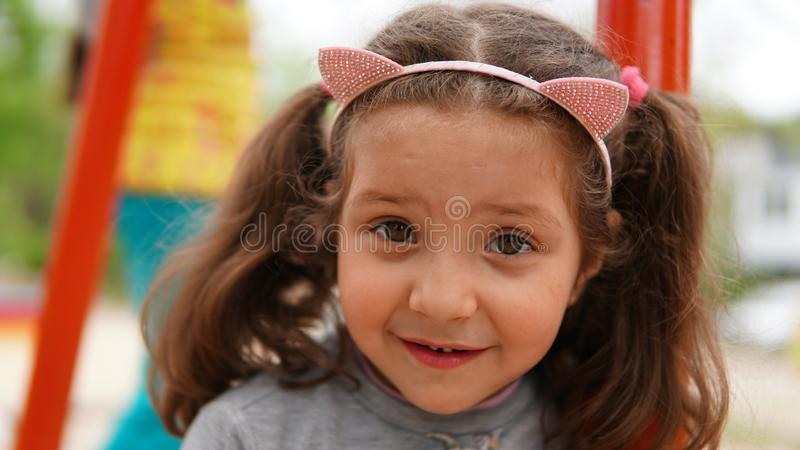 Portrait of Happy Smiling Child Girl Playing at Playground in Summer royalty free stock photo