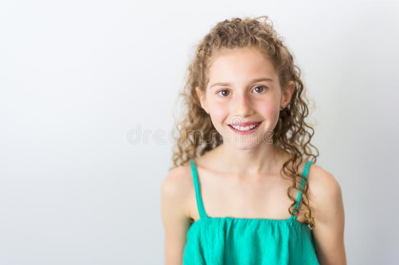 Portrait of happy, smiling, confident 9 years old girl with curly hair, isolated on gray royalty free stock photo