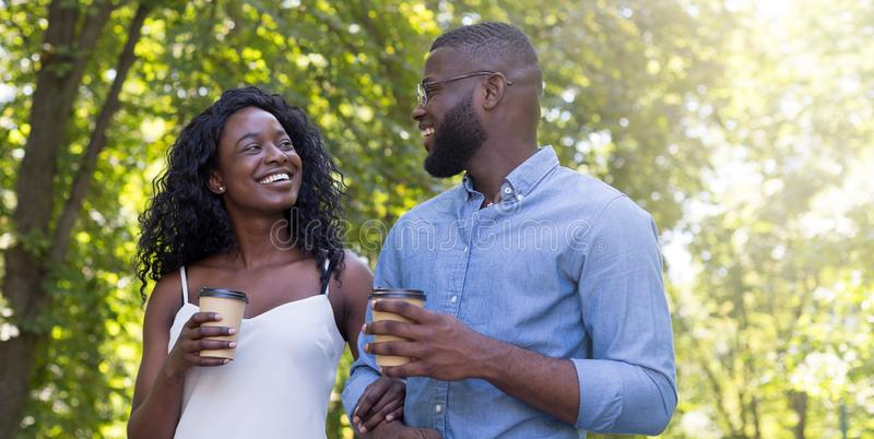 Portrait of happy smiling couple drinking and enjoying coffee walking in nature stock image