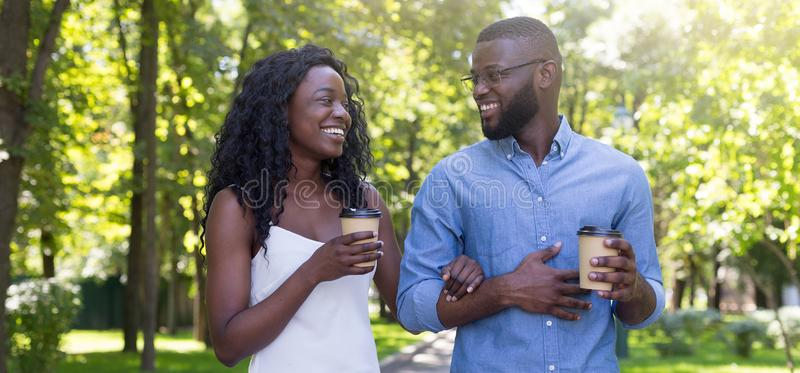 Portrait of happy smiling couple drinking and enjoying coffee walking outdoors stock photos