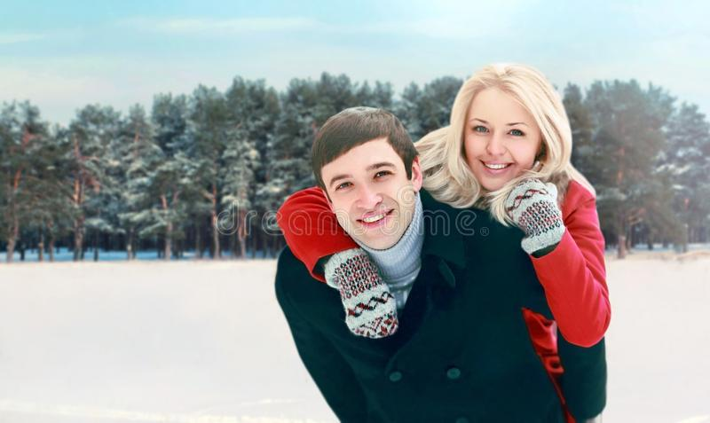 Portrait happy smiling couple having fun at winter day, man giving piggyback ride to woman. Portrait happy smiling couple having fun at winter day, men giving royalty free stock photos