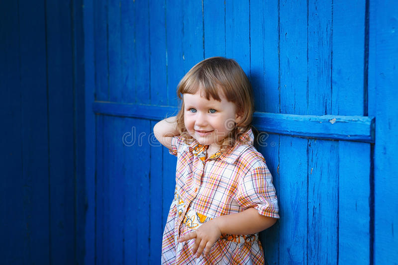Portrait of happy smiling cute little girl against the blue wall royalty free stock photography
