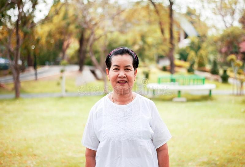 Portrait of a happy and smiling elderly asian woman standing outdoor royalty free stock image