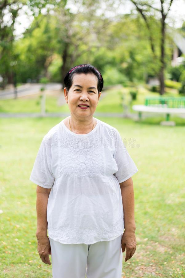 Portrait of a happy and smiling elderly asian woman standing at public park royalty free stock image