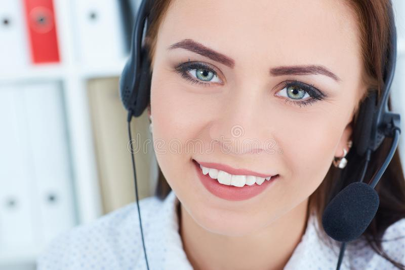 Portrait of happy smiling female customer support phone operator with headset on head at workplace. stock photos