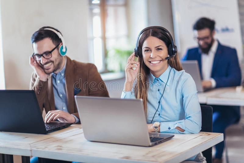 Portrait of happy smiling female customer support phone operator stock photo