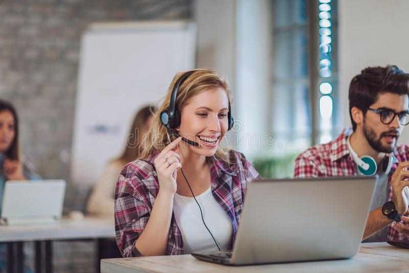 Portrait of happy smiling female customer support phone operator. At workplace stock photo
