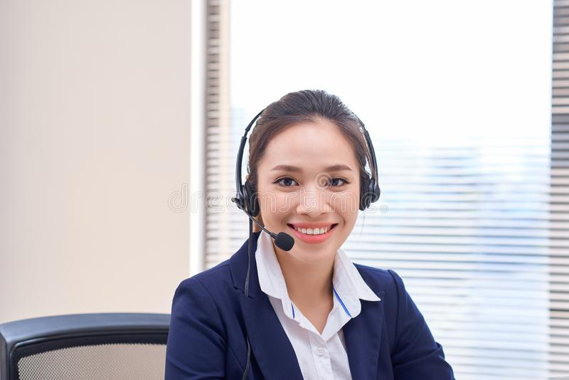 Portrait of happy smiling female customer support phone operator at workplace. Asian royalty free stock images