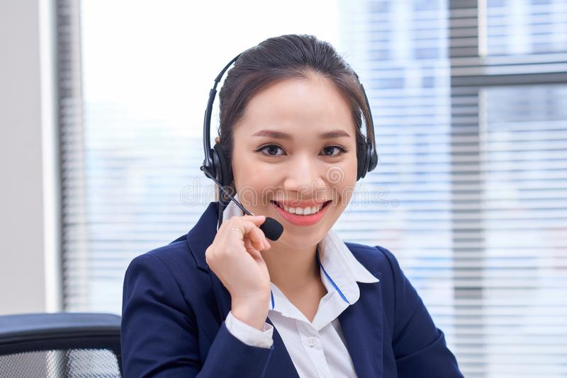 Portrait of happy smiling female customer support phone operator at workplace. Asian.  royalty free stock image