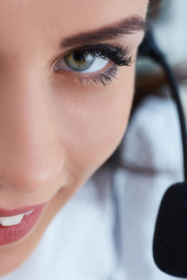 Close-up portrait of happy smiling female customer support phone operator at workplace. royalty free stock photos