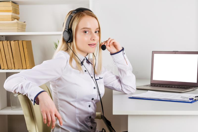Portrait of happy smiling female customer support phone operator at workplace royalty free stock photo